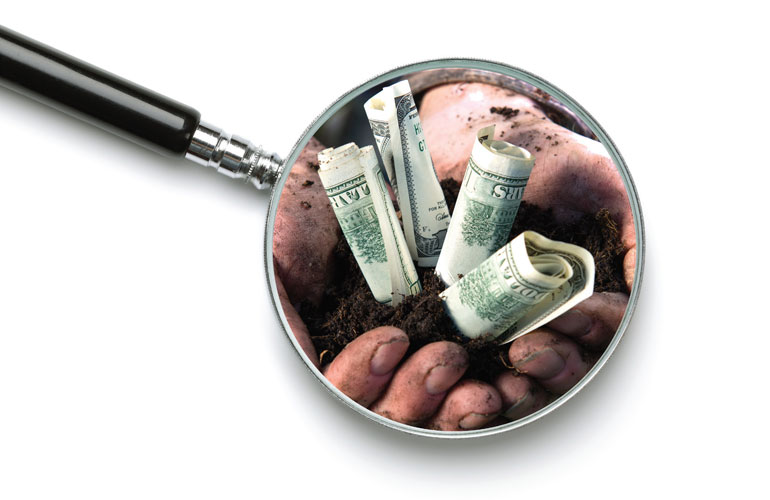 hands-with-soil-dollar-notes-and-a-magnifying-glass